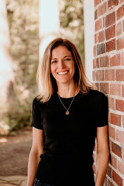 Dr. Lisa Arthur smiling next to a brick wall