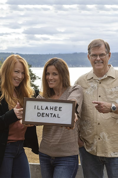 Our three Illahee Dental specialists holding a sign